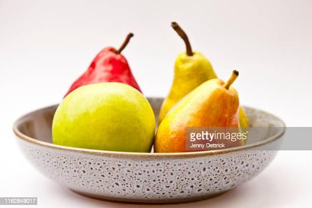 pears and apple in fruit bowl - 果物の盛り合わせ ストックフォトと画像
