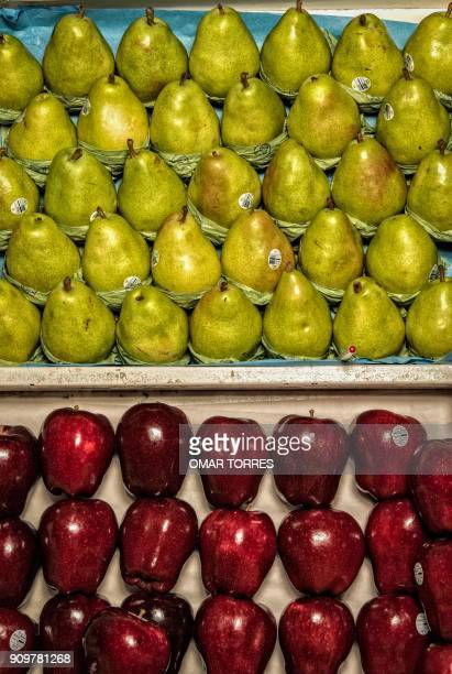Pears and apples are sold at a stand in the San Juan Market in Mexico City on November 3 2016 / AFP PHOTO / Omar TORRES