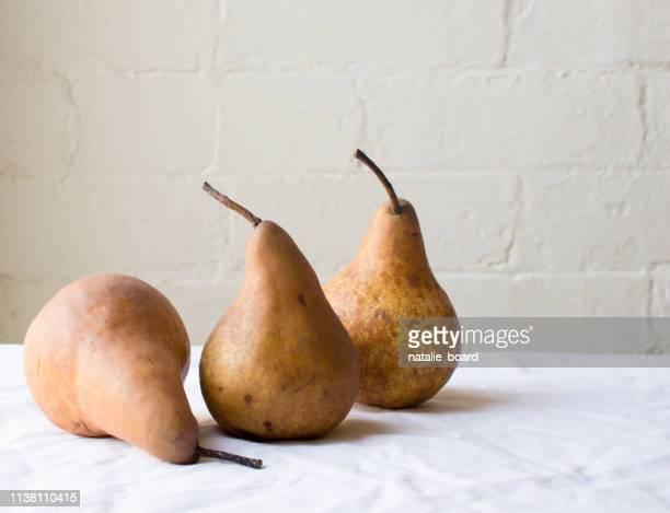 pears on table against wall - maduro fotografías e imágenes de stock