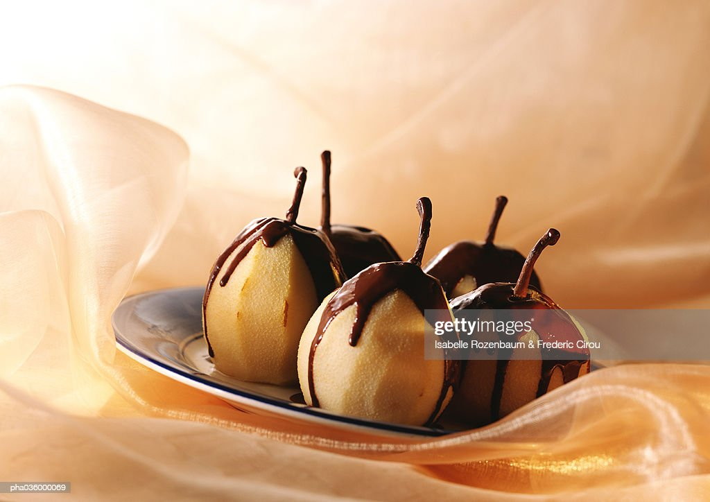 Pears semi-covered with melted chocolate, on plate : Stockfoto