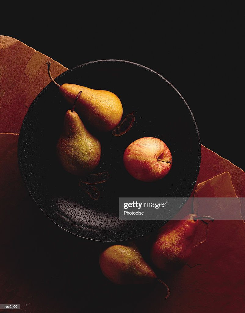 pears sit inside and outside of a black bowl on a red stone table : Foto de stock