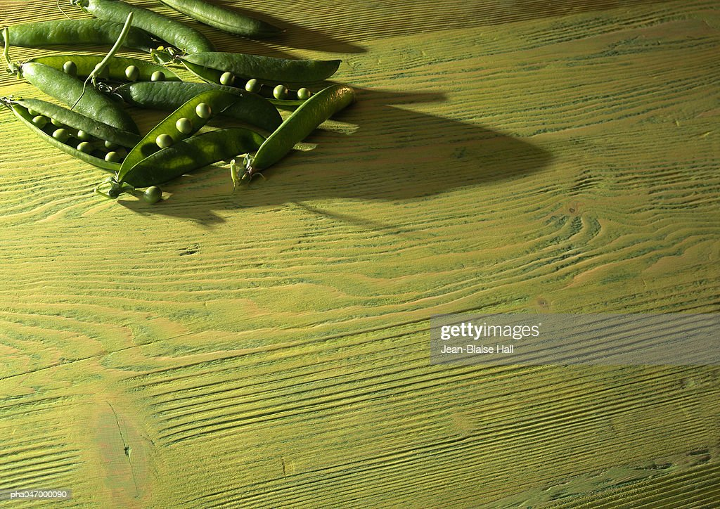 Peas in open pods on wood table, off centered : Stockfoto