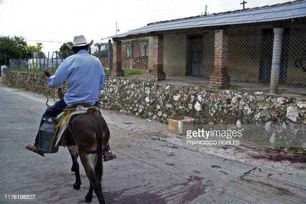 A peasant atop a donkey passes by the place where a confrontation between the Mexican Army and armed civilians took place in Tepochica Iguala...