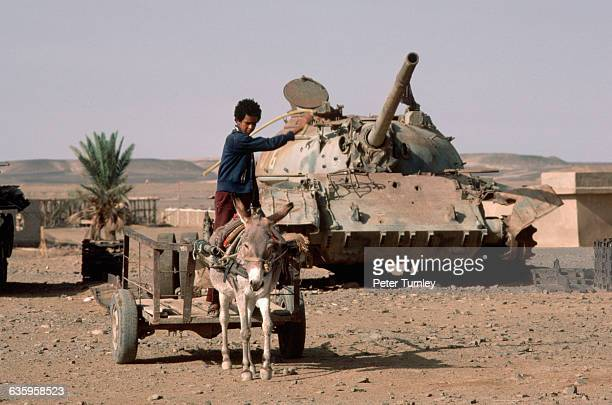 A peasant boy drives a donkey cart through the desert in front of a T55 Russian tank taken from the Polisario The Polisario are a guerilla group of...