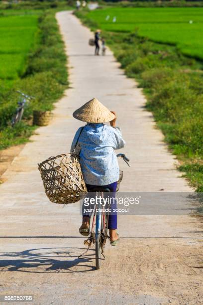 Peasant on a bicycle, on a road, in Phong Nha (Vietnam)