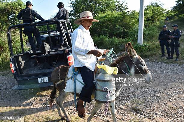 A peasant rides his donkey near to a Federal Police special unit team at a checkpoint near to the place where a new mass grave was found in the 27 de...