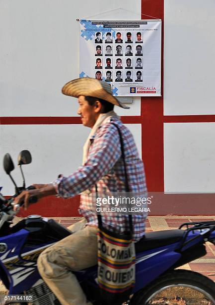 A peasant rides his motorcycle next to a poster with photographs of people buried in unidentified condition in the cemetery of La Macarena Meta...