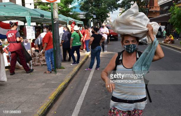 Peasant woman carries her production on her head on the Day of the Paraguayan Woman, in Asuncion, on February 24, 2021. - Peasant women arrived in...