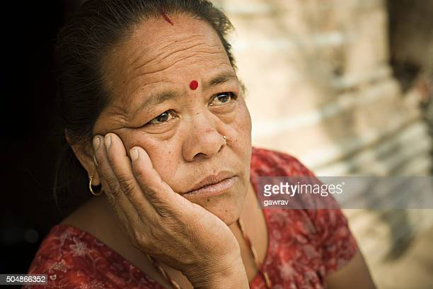 Peasant woman holding head and looking up with blank expression.