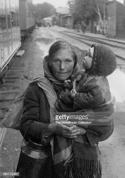 Peasant woman in worn winter clothing holding a young child and metal feed can standing beside a row of train carriages during World War II Eastern...