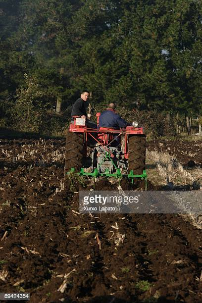 Peasants cultivating the ground with tractor near the river Mino in Outeiro de Rei Terra Cha Lugo