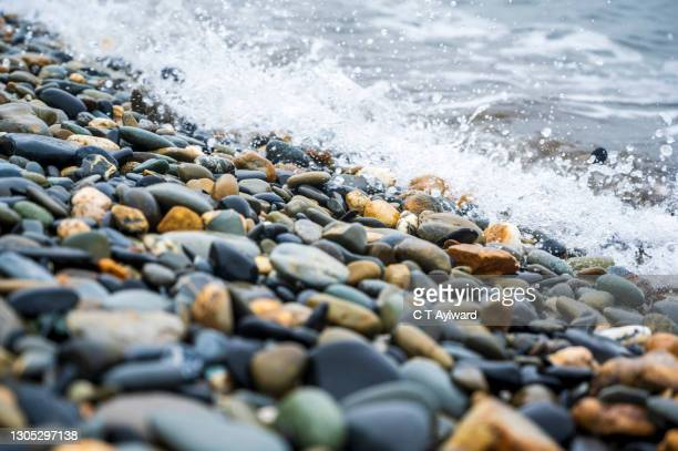 pebble beach and rippling waves - rock stock pictures, royalty-free photos & images