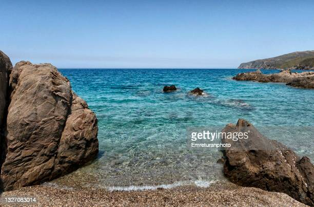 pebble beach between rocks at badembükü,aegean turkey. - emreturanphoto - fotografias e filmes do acervo
