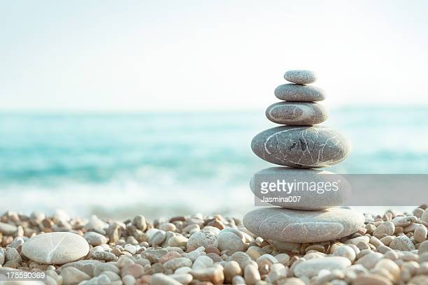 pebble on beach - wellbeing stock pictures, royalty-free photos & images