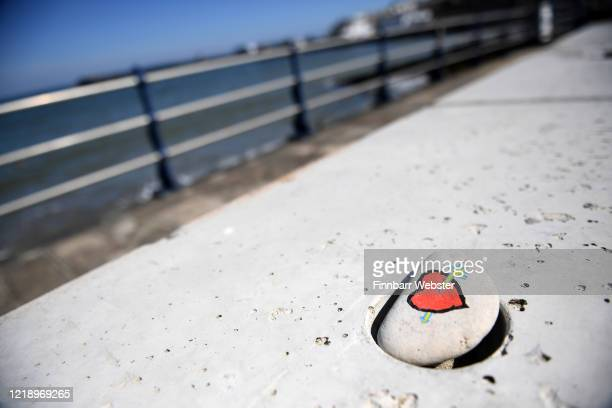 Pebble with a decoration of a love heart is seen on the seafront on April 15, 2020 in Swanage, United Kingdom. The Coronavirus pandemic has spread to...