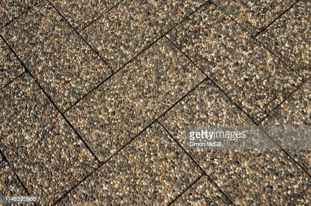 pebblecrete exposed aggregate and concrete rectangular paving stones arranged in a herringbone pattern - herringbone floor stock photos and pictures