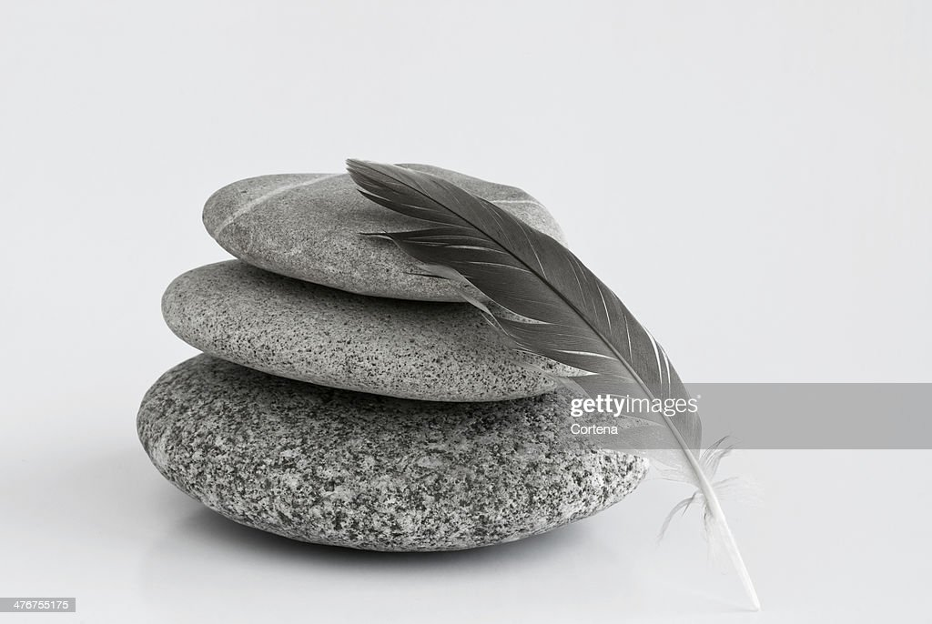 Pebbles and a feather : Stock Photo