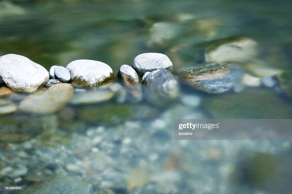 Pebbles and arranged stones in river water : Stock Photo
