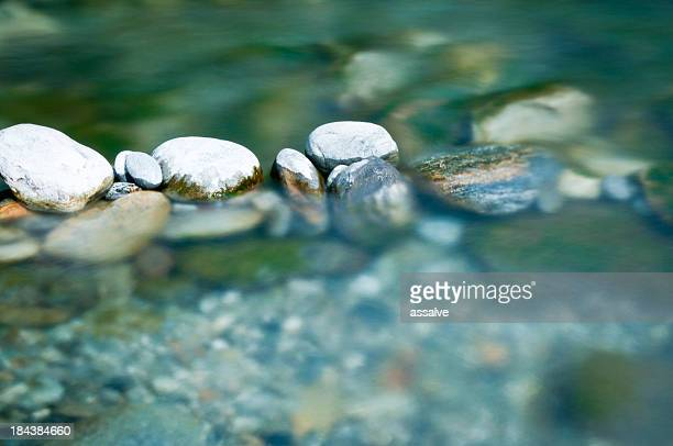 pebbles and arranged stones in river water - rivier stockfoto's en -beelden