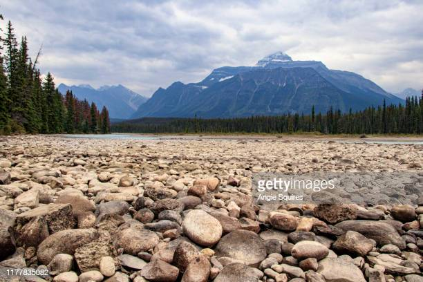 pebbles in foreground of river bank in dramatic canadian landscape of jasper national park - pebble stock pictures, royalty-free photos & images