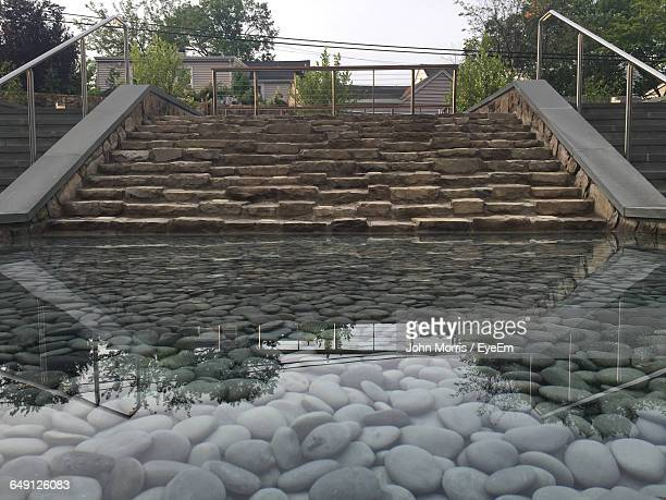 pebbles in lake by staircase at park - bethesda maryland stock photos and pictures