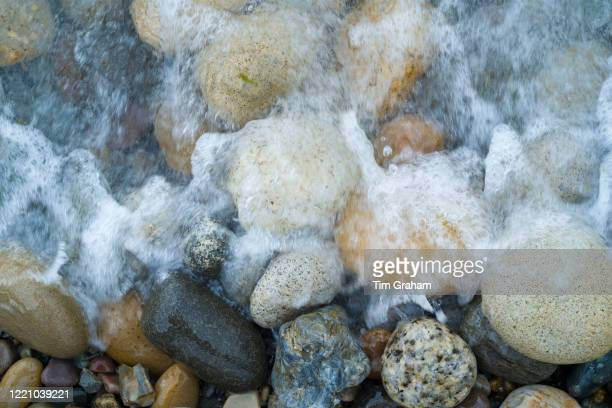 Pebbles in pastel shades of colour as wave soaks them on the seashore on Isle of Arran, Scotland.