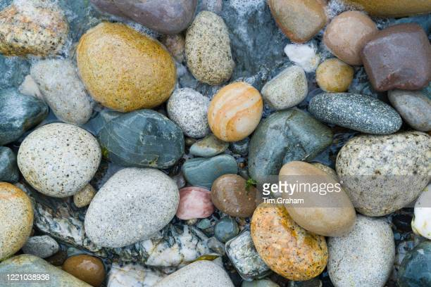 Pebbles in pastel shades of colour form curvy shapes on the seashore on Isle of Arran, Scotland.