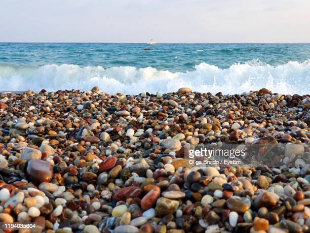 pebbles on beach against sky - pebble beach california stock pictures, royalty-free photos & images