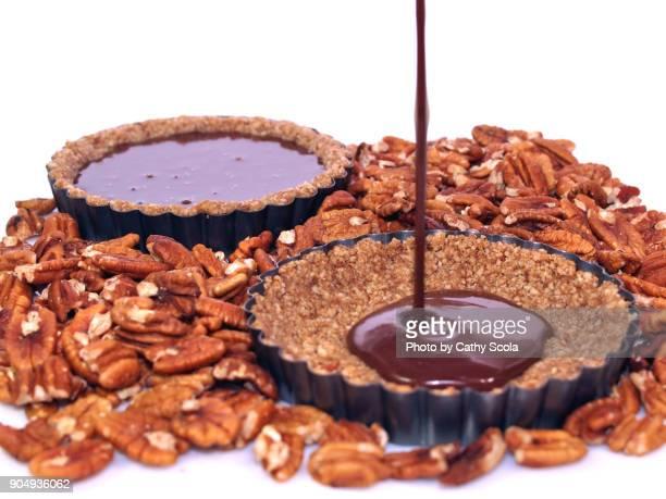 pouring chocolate into pecan tart shells
