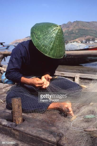 Pecheur reparant ses filets a Vung Tau Viet Nam
