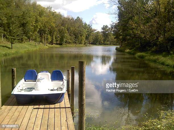 pedal boat on jetty in river amidst trees - pedal boat stock pictures, royalty-free photos & images