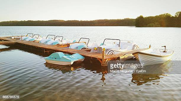 Pedal Boats Moored By Jetty In Lake