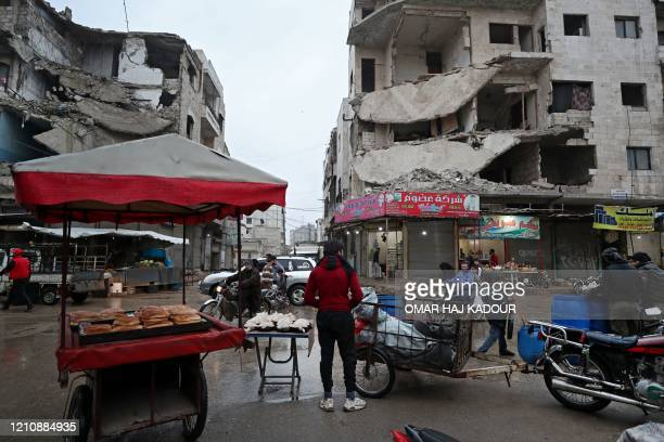 Peddlar sells bread and pastries from a cart in the rain in a square in Syria's northwestern city of Idlib on April 24 on the first day of the Muslim...