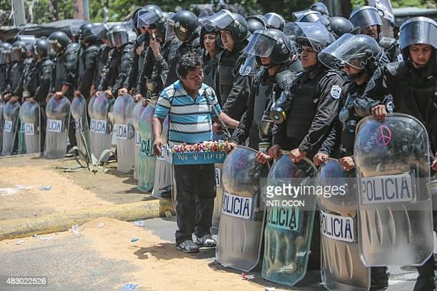 A peddler offers his marchandise to a line of riot police during a protest against the electoral system in Managua on August 5 2015 AFP PHOTO / Inti...