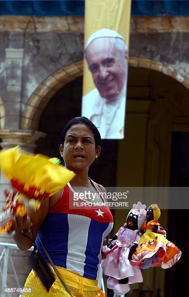 A peddler sells dolls by a poster of Pope Francis in Havana's Cathedral square on September 17 2015 The pope is visiting Cuba from September 19 to 22...