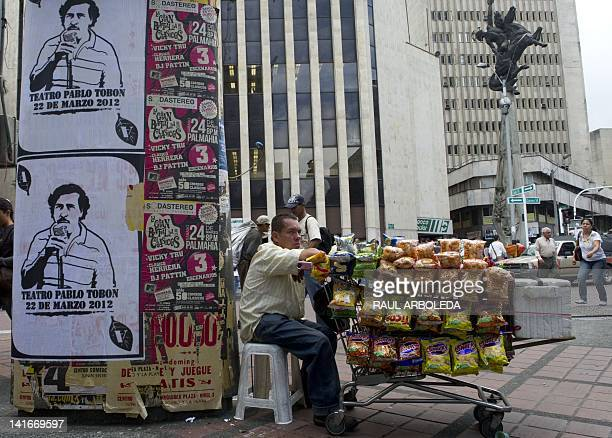 Peddler stays by posters with the image of deceased Colombian drug lord Pablo Escobar along a street of Medellin, Antioquia department, Colombia, on...