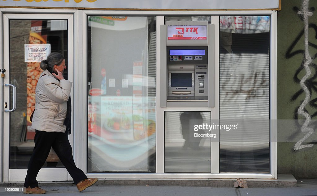 A pederstrian passes an automated teller machine (ATM) operated by TTK Banka AD in central Skopje, Macedonia, on Sunday, March 17, 2013. Macedonia's economy contracted by a real 0.3% on the year in 2012, compared to a growth of 2.8% a year earlier, an estimate released by the country's statistics office showed. Photographer: Oliver Bunic/Bloomberg via Getty Images