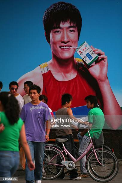 Pedestrains walk past a billboard featuring Olympic 110m hurdles champion Liu Xiang promoting a brand of milk on August 2 2006 in Hohhot of Inner...