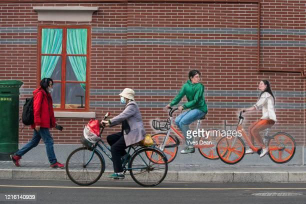 A pedestrian and a biker wearing protective masks by a mural wall on April 01 in Shanghai China Shanghai has reopened most of outdoor public...