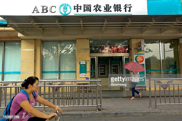 A pedestrian and a cyclist pass a branch of the Agricultural Bank of China Ltd in Beijing China on Tuesday Aug 28 2012 Agricultural Bank of China is...