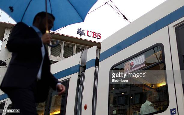 A pedestrian and a tram pass the UBS Group AG's headquarters in Zurich Switzerland on Thursday July 23 2015 UBS Group AG and Morgan Stanley increased...