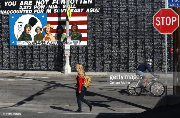 DAY A pedestrian and bicyclist make their way past a mural that features the names of some of the 2273 Vietnam veterans that are still MIA from the...