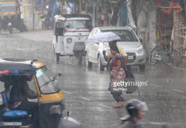 Pedestrian and commuters look on the road as they hold umbrella to protect them from the monsoon rain as it lashes in all over the eastern India and...