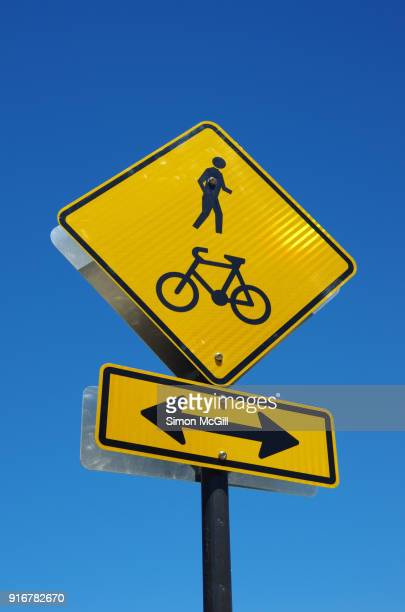 pedestrian and cyclist crossing road warning sign - crossing sign stock pictures, royalty-free photos & images