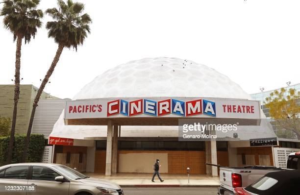 Pedestrian and traffic pass in front of the Cinerama Dome in Hollywood on April 13, 2021. ArcLight Cinemas and Pacific Theaters said late Monday they...