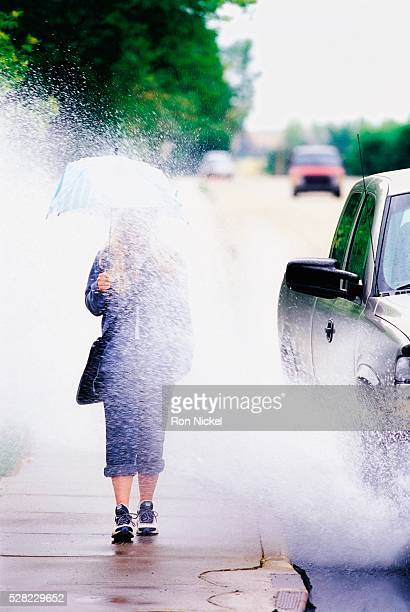 Pedestrian Being Splashed with Puddle Water from the Street
