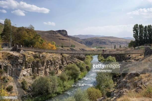 pedestrian bridge across muradiye river in autumn. - emreturanphoto stock pictures, royalty-free photos & images