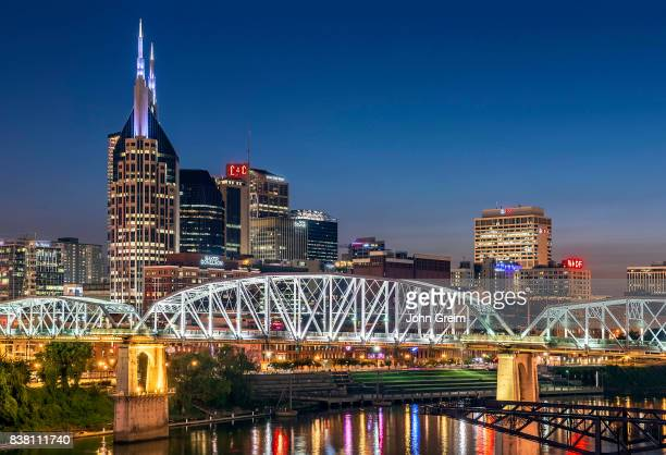 Pedestrian bridge over the Cumberland river and the lights of the Nashville city skyline at dusk