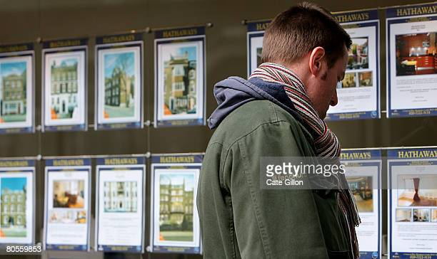 A pedestrian browses properties on display in the window of an estate agent on April 8 2008 in London England The Halifax has announced that house...