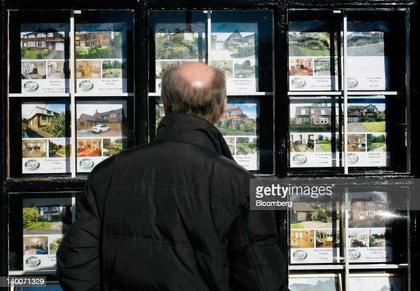 A pedestrian browses residential property on display in the window of an estate agent in Worsley UK on Thursday Feb 23 2012 UK house prices held...